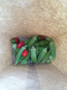 paper bag of okra with some red jalapeños thrown in for fun